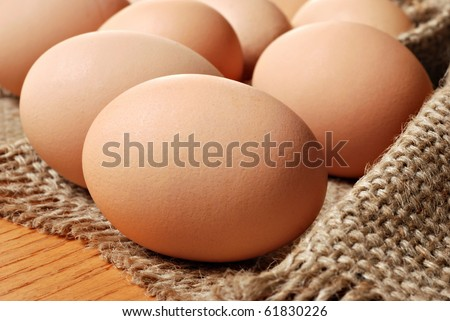Fresh brown cage free eggs on burlap.  Macro with shallow dof.