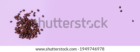 Fresh brown coffee beans randomly scattered on purple background. Banner. Flat lay, top view Photo stock ©