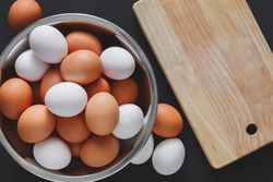Fresh brown eggs in bowl and wooden cutting board isolated at black background with copy space. Top view. Natural healthy organic food, cooking concept