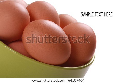 Fresh brown eggs in green bowl. Isolated over white