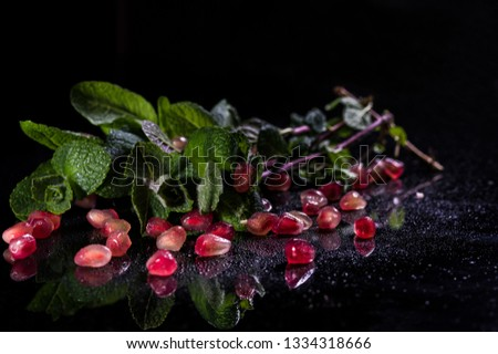 Fresh bunch of mint. Scattered grains of pomegranate. Water drops. Bright and saturated photos. #1334318666