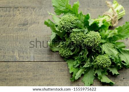 Fresh bunch of raw green organic broccoli rabe- rappini on black wooden background Foto stock ©