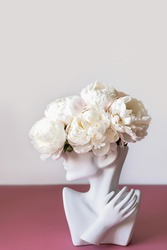 Fresh bunch of white peonies in vase in shape of womens face on dusty pink background. Trendy Ceramic Vase of human head, Handmade Modern Statue Art Flower Vase. Card Concept, copy space for text