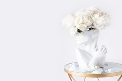 Fresh bunch of white peonies in vase in shape of womens face on light background. Trendy Ceramic Vase of human head, Handmade Modern Statue Art Flower Vase. Card Concept, copy space for text