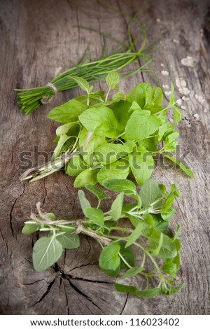 Fresh bunches of herbs on wooden table
