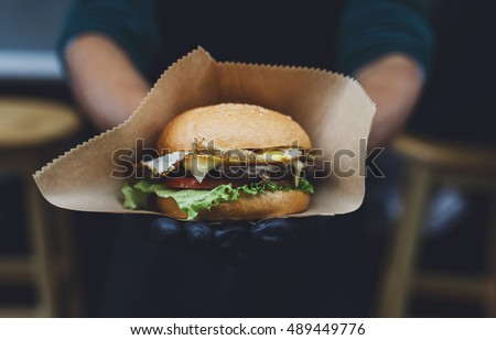 Fresh burger cooked at barbecue outdoors in craft paper. Cookout american bbq food. Big hamburger with steak meat and vegetables closeup with chef unfocused at background. Street food, fast food.