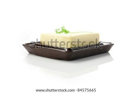 fresh butter in the butter dish on white background