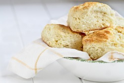 Fresh buttermilk southern biscuits or scones from scratch in a white bowl.