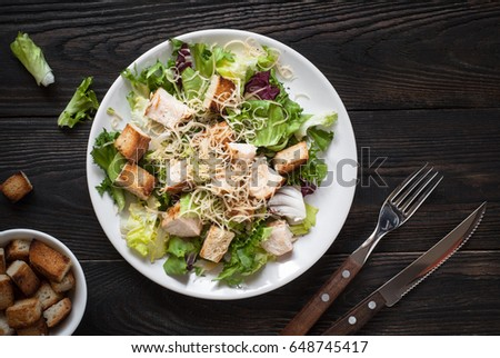 Fresh caesar salad in white plate on  dark wooden table. Top view. #648745417