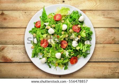 Fresh caesar salad on white plate on wooden planks