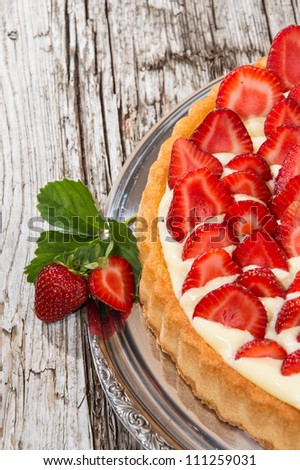 Fresh Cake on a silver Plate against wooden background