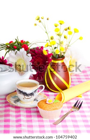 Fresh cake; White kettle; cup of tea; and yellow flowers on a checkered tablecloth