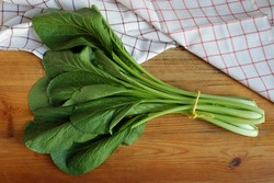Fresh cantonese vegetables tied into a bundle, placed on a brown wooden plate and decorated with hand towels. Cantonese are vegetables that Asian people use to cook in soups or noodles.