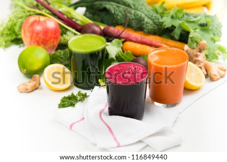 Fresh Carrot, Beets, and Greens Juices on White Background