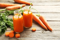 Fresh carrot juice in bottles on a grey wooden table