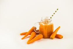 Fresh carrot juice in mason jar and straw isolated