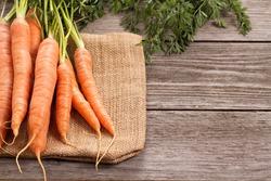 Fresh carrot with green leaves on jute bag