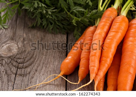 Fresh Carrot With Green Leaves On Wooden Table