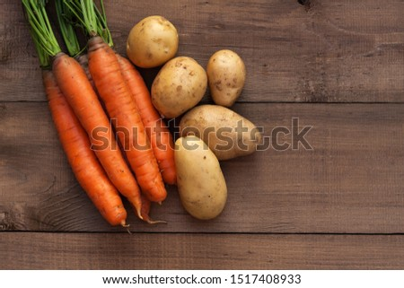 Fresh carrots and potatoes on a wooden background. Harvest season #1517408933