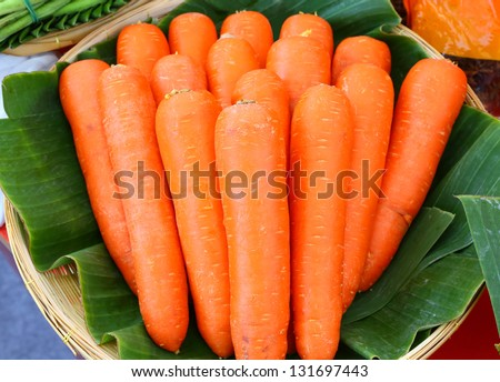 Fresh carrots in basket against banana leaf