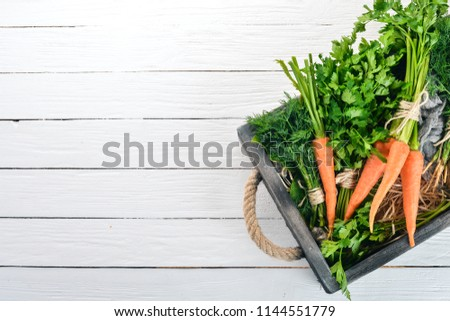 Fresh carrots, parsley and dill. Organic food. On a white wooden background. Top view. Free space for text.