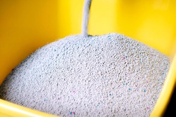 Fresh Cat Sand Pouring into a Yellow Litter Box