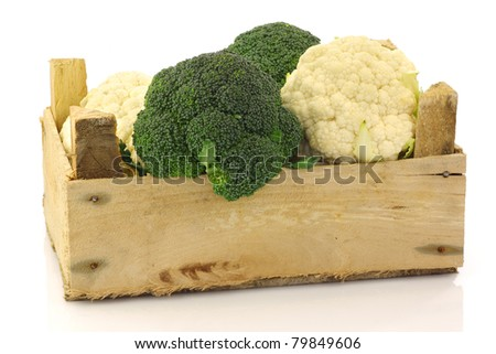 Fresh cauliflower and broccoli in a wooden crate on a white background