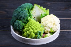 Fresh cauliflower, broccoli and romanesco broccoli on a round tray. the concept of a healthy lifestyle. top view. copy space.