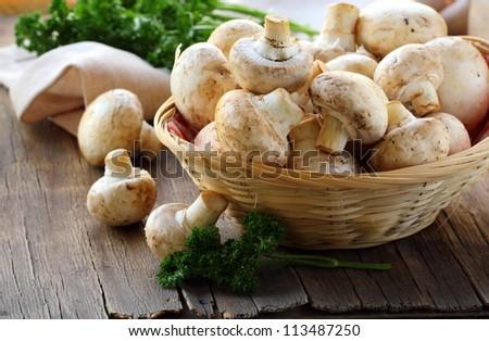 Fresh champignon mushrooms in a wicker basket