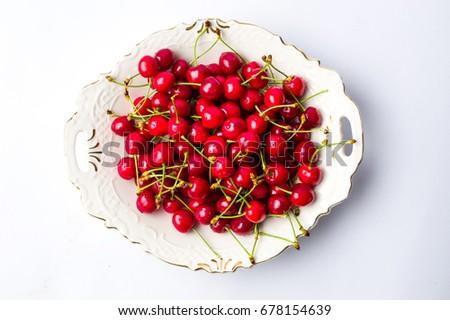 Fresh cherries in a white ceramic bowl #678154639