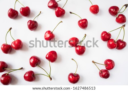Fresh cherries scattered on white. Cherries on a white background. Cherry fruit. Creative fresh cherry pattern background with copy space. Top view. Sprinkled cherry on white background.