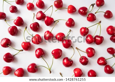 Fresh cherries scattered on white. Cherries on a white background. Fresh cherry. Cherry fruit. Cherries with copy space for text. Top view. Background of cherries.Sprinkled cherry on white background.