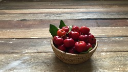 Fresh Cherry fruits in the wicker basket, on old wood table top, natural dimly light, selective focus. High vitamin C fruits.