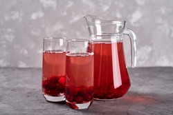 Fresh cherry lemonade in glasses and jug on gray table background, copy space. Cold summer drink. Berry cocktail