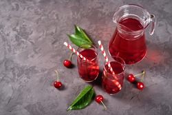 Fresh cherry lemonade in glasses with paper straws and jug on gray table background, copy space. Cold summer drink. Berry cocktail