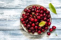Fresh cherry on plate on wooden blue background. fresh ripe cherries. sweet cherries.