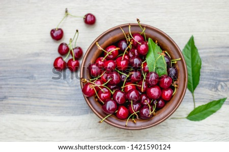 Fresh cherry on plate on wooden grey background. fresh ripe cherries. sweet cherries. Sweet cherries bowl with leaves.