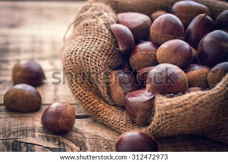 fresh chestnuts in jute sack on the old wooden background