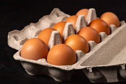 Fresh chicken eggs in a paper container. Dairy products prepared for serving. Dark background.