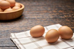 fresh  chicken eggs in a wooden bowl on a black wooden table, selective focus.