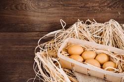 Fresh chicken eggs on a wooden rustic background. Fresh organic eggs in egg carton box. Close up of eggs in a nest box on a wooden table and sackcloth. Happy Easter and natural food background.