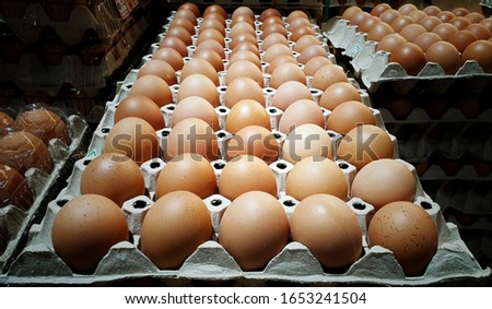 Fresh chicken eggs pile up on the tray at supermarket.