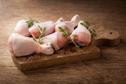 fresh chicken meat with rosemary and spices on wooden board