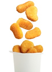 Fresh chicken nuggets falling into container on white background