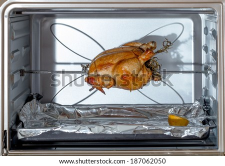 Fresh chicken, trussed, stuffed with herbs and cooking on a spit in a domestic oven