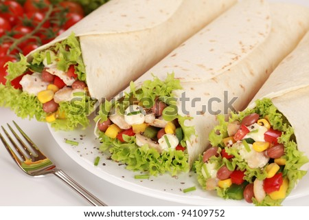 Fresh chicken wrap sandwiches filled with beans, lettuce and corn