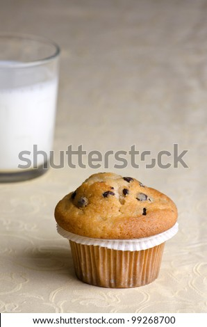 Fresh chocolate chip muffin and a glass of milk in the background