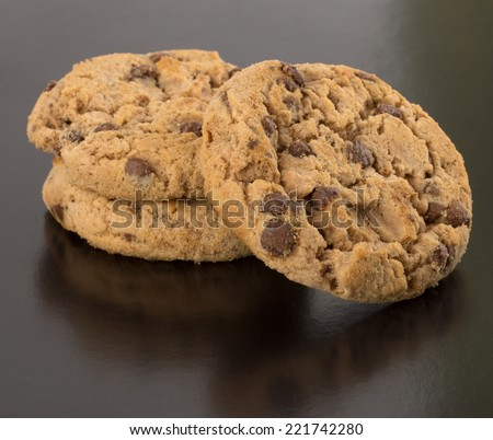 Fresh chocolate cookies with pieces of chocolate isolated on black background