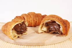 Fresh chocolate croissant on a wood traditional plate