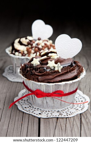 Fresh chocolate cupcakes decorated with white hearts and a red ribbon on a wooden floor background - stock photo